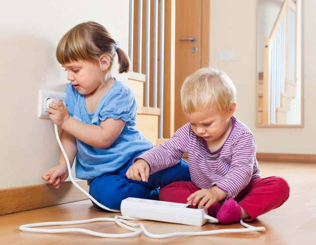 Two children playing with electricity on floor at home