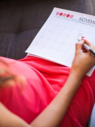 Lady writing her due date on a calendar