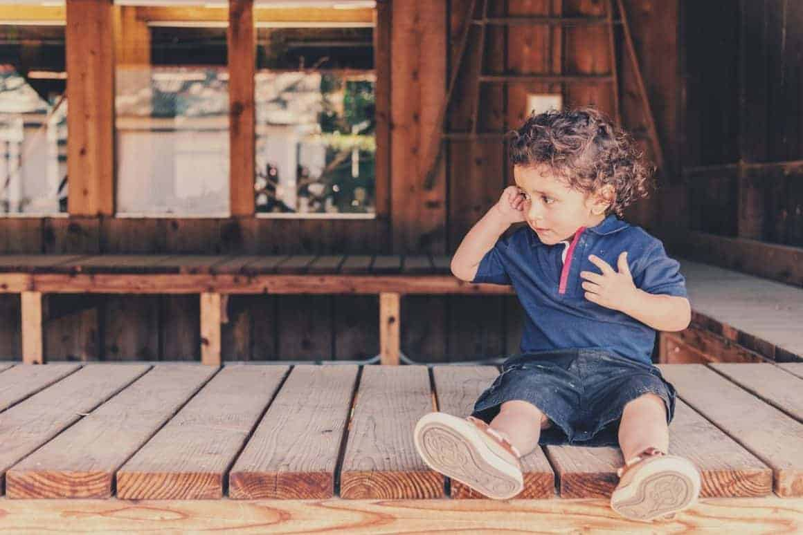 Little boy sitting on front porch