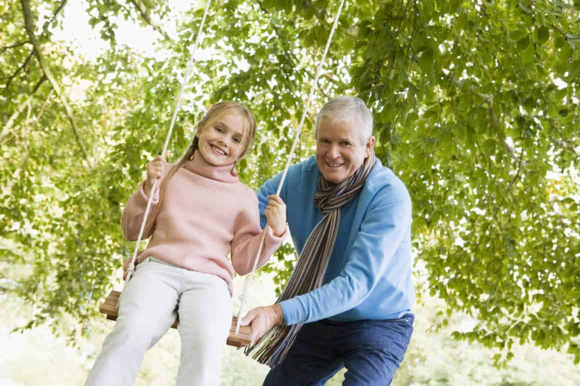 grandfather-pushing-granddaughter-on-swing-and-smiling