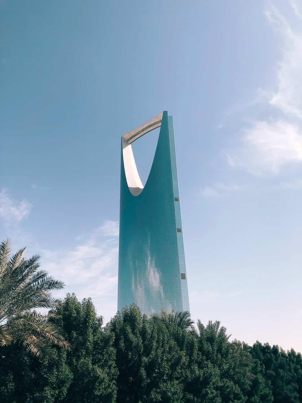 high rise building behind trees under blue sky in Riyadh Saudi Arabia