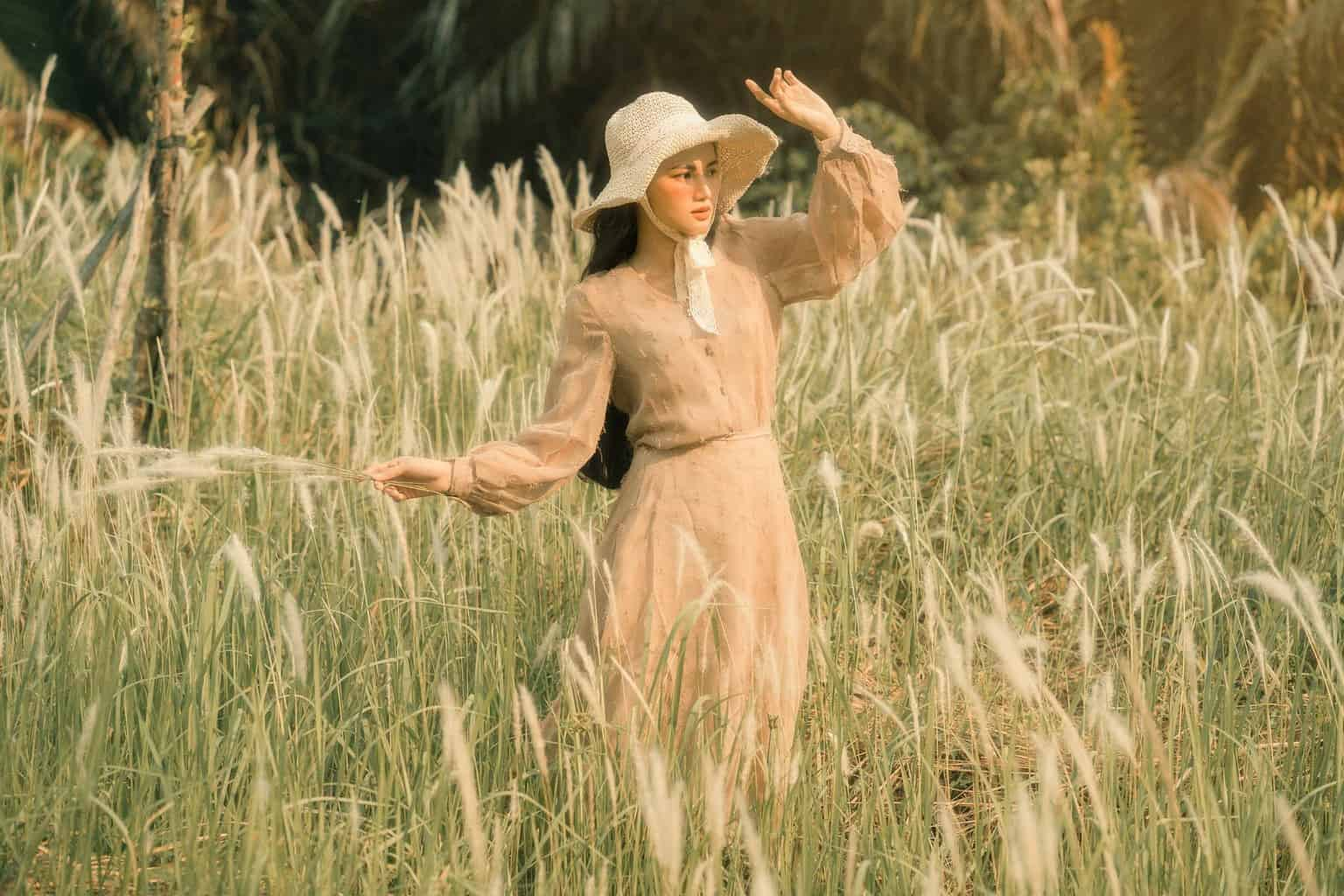 woman in hat among grass in field