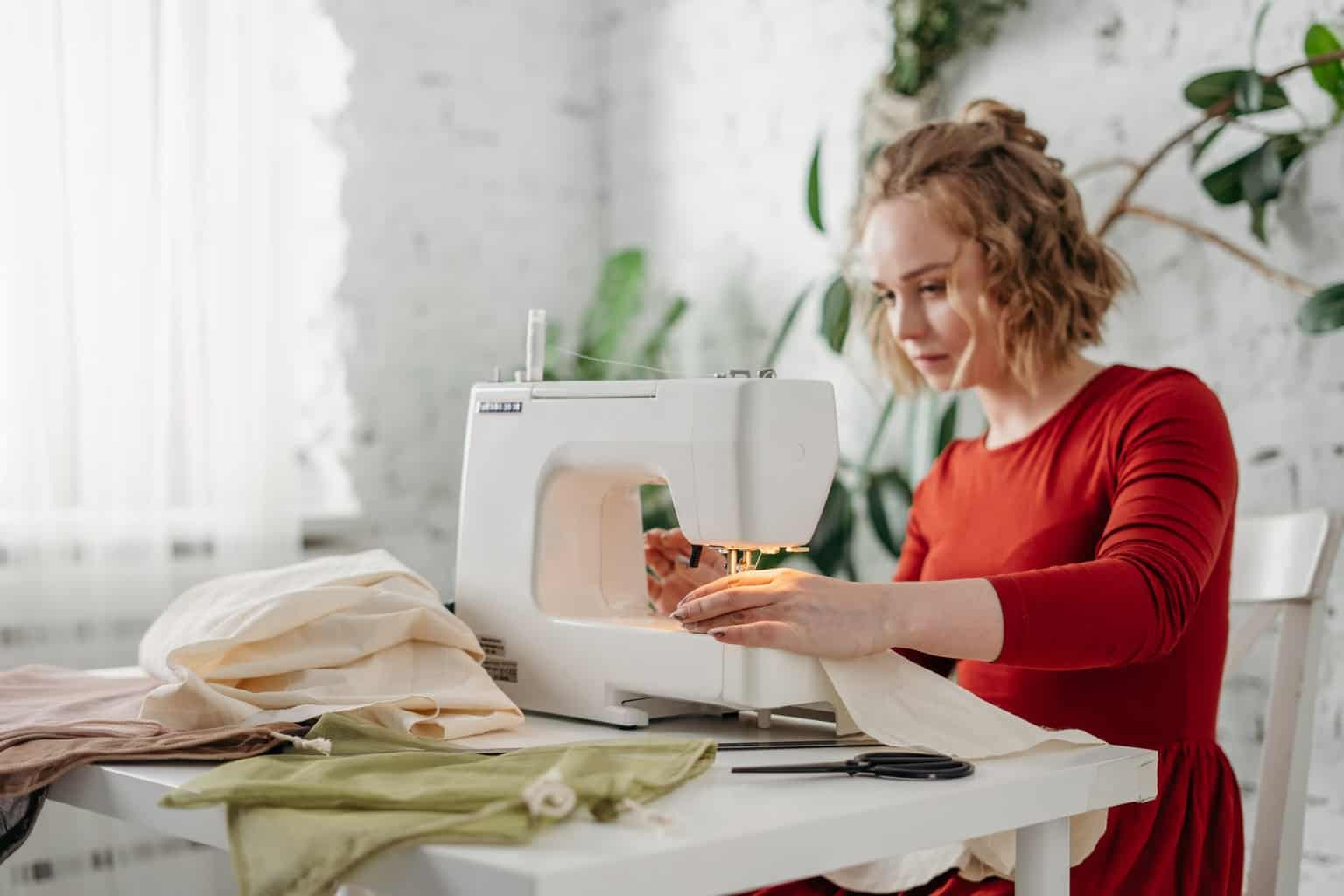 woman sewing while sitting on chair