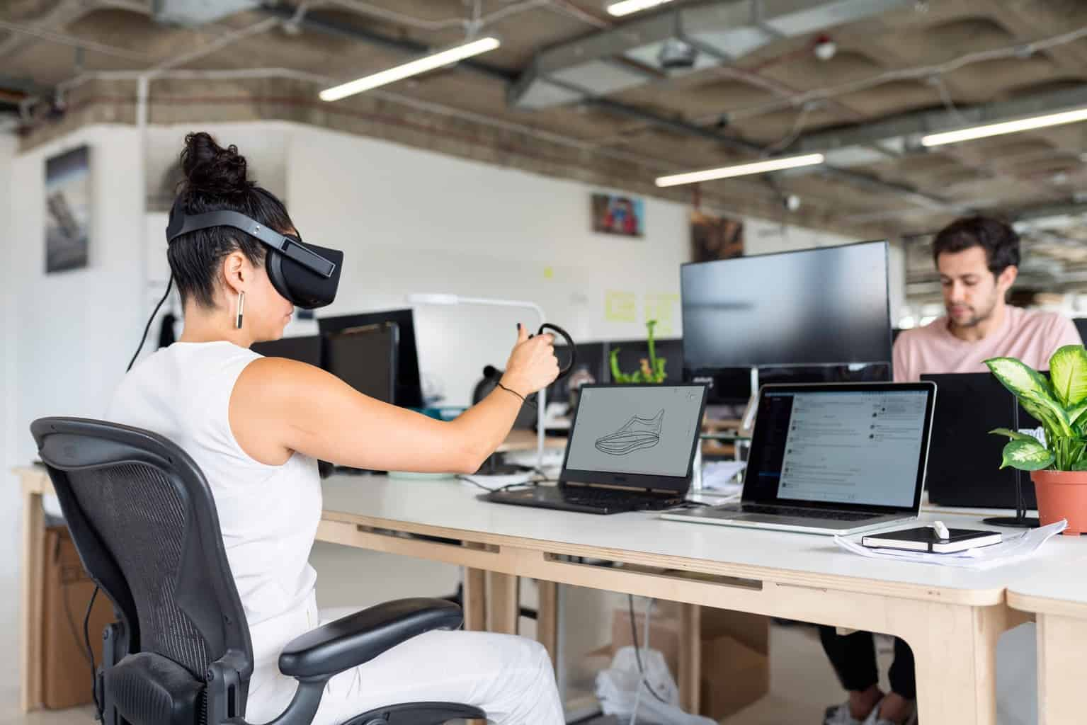 woman in white tank top using black laptop computer with vr headset