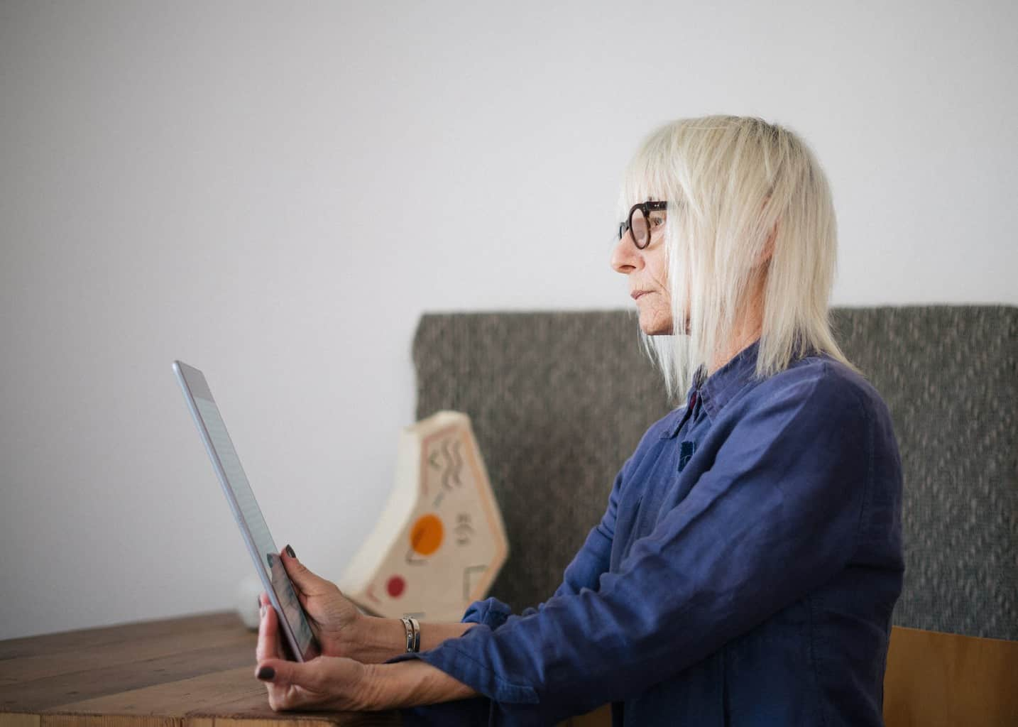aged woman using tablet while sitting at home