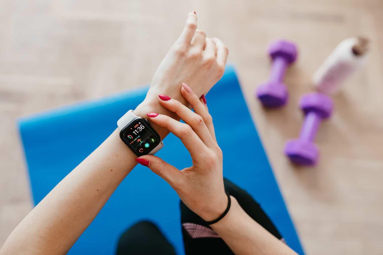anonymous sportswoman checking smart watch and sitting on mat