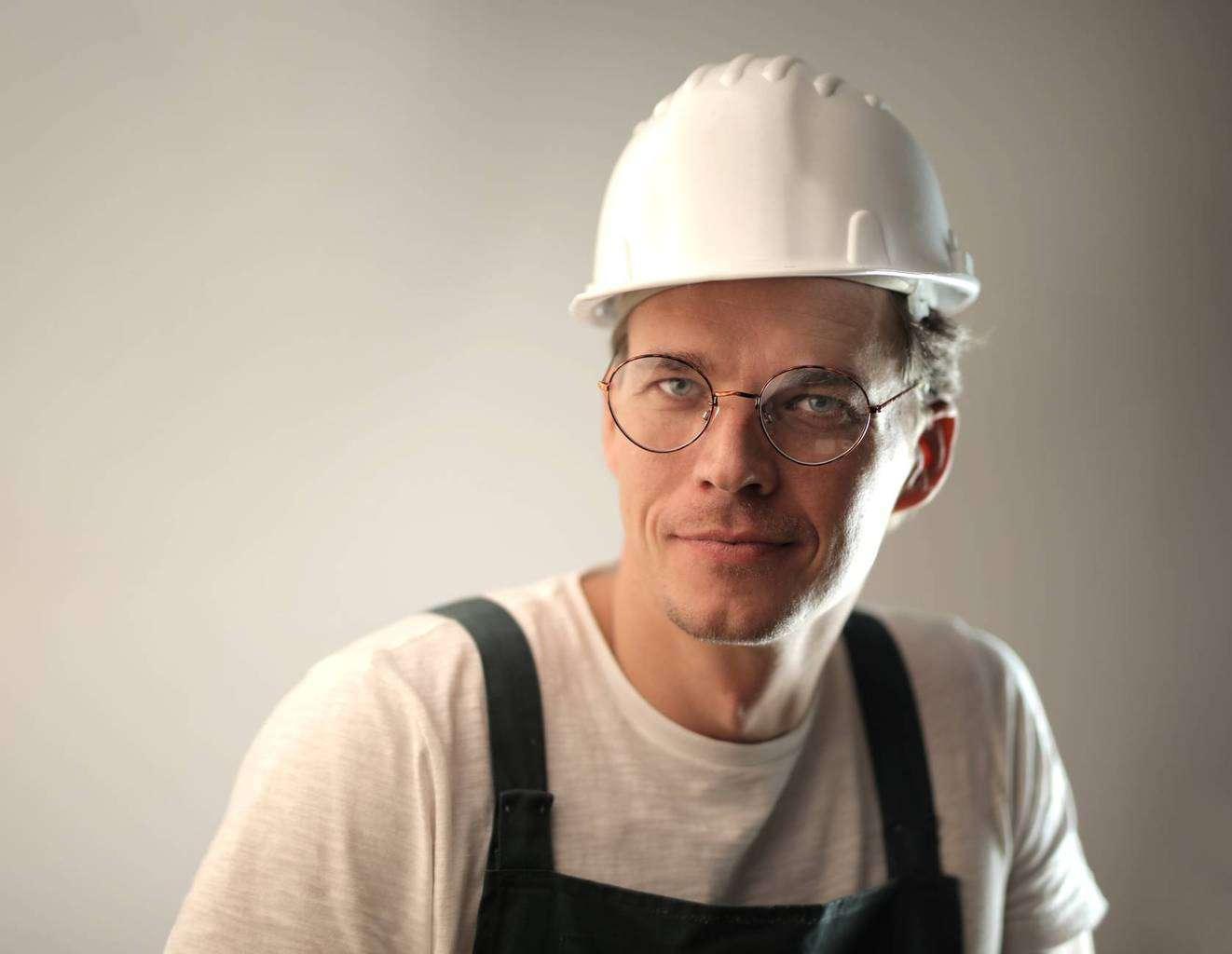 smiling male worker in construction helmet in studio