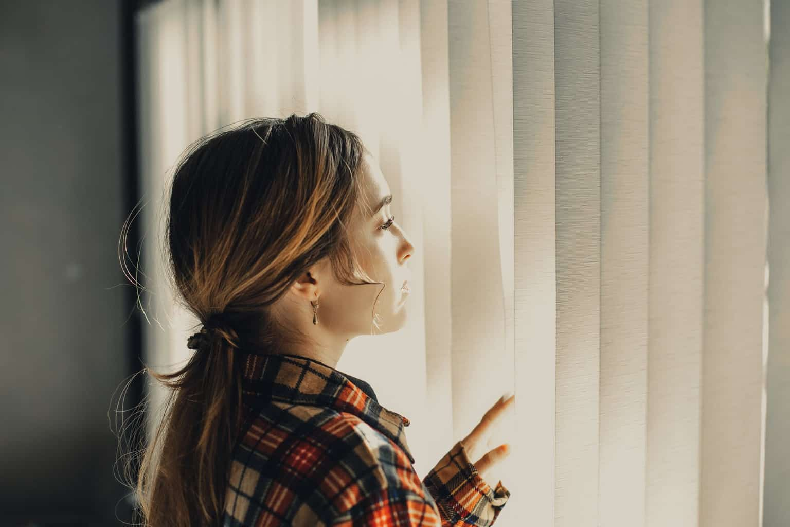 thoughtful young woman looking through blinds of window in daylight