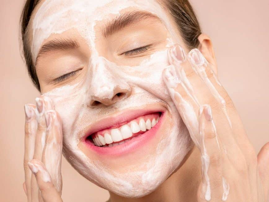 woman with white facial soap on face