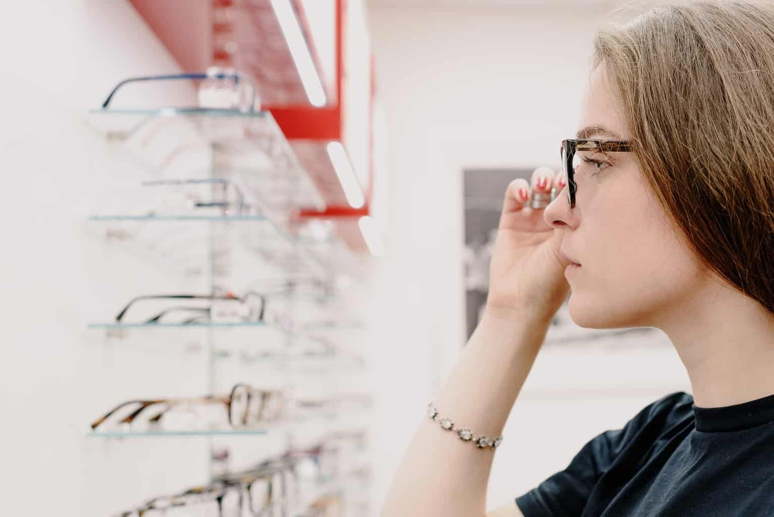 young woman adjusting glasses in optical store