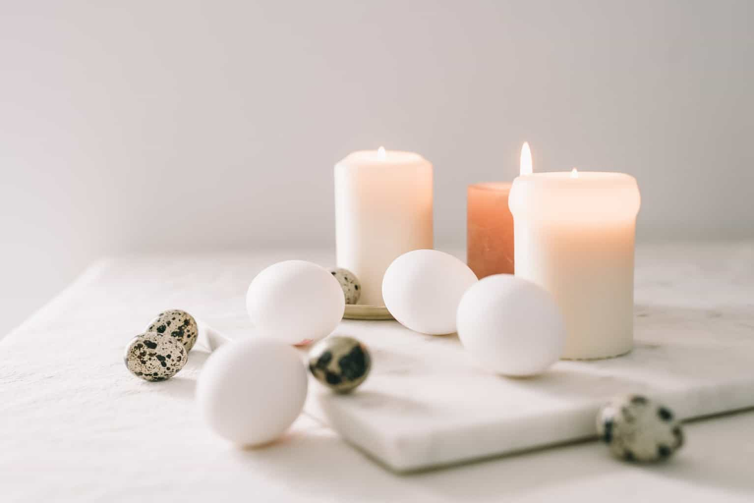 white eggs and quail eggs beside lighted candles
